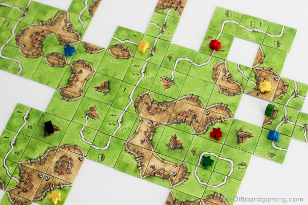 Carcassonne is a tile placement game with simple components and pretty simple rules... but endless map building variations.